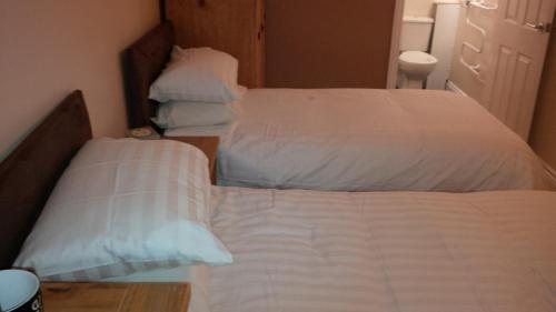 A bed or beds in a room at The Old Royal George Inn