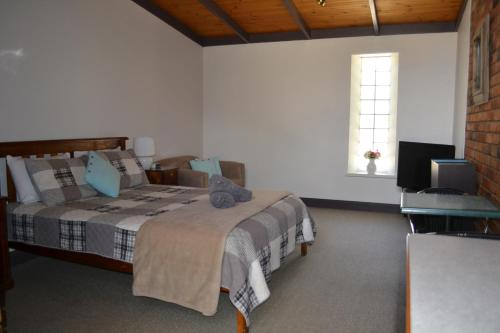 A bed or beds in a room at Colonial Motel