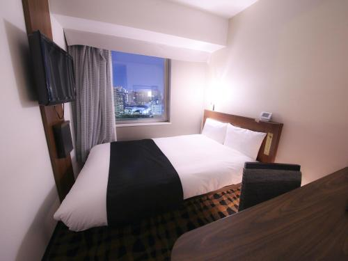 A bed or beds in a room at APA Hotel Nihombashi Hamacho-eki Minami