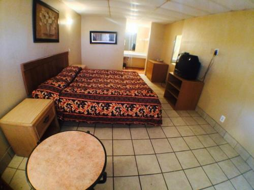 A bed or beds in a room at Austin Motor Inn