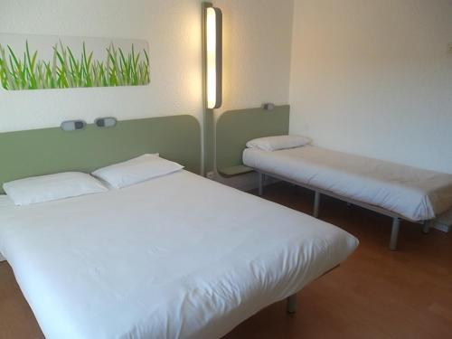 A bed or beds in a room at Ibis Budget Marseille Est Saint-Menet La Valentine