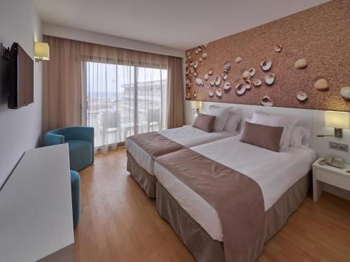A bed or beds in a room at BQ Can Picafort Hotel
