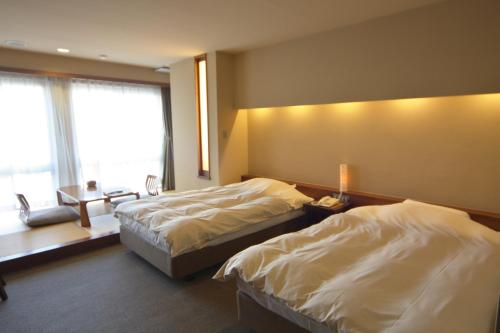 A bed or beds in a room at Miyahama Grand Hotel
