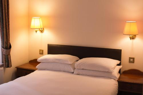 A bed or beds in a room at Abbey Lodge Hotel