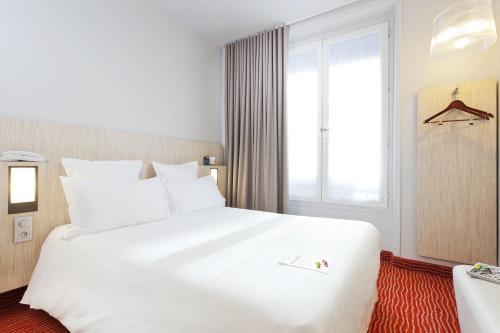 A bed or beds in a room at Libertel Gare de L'Est Francais