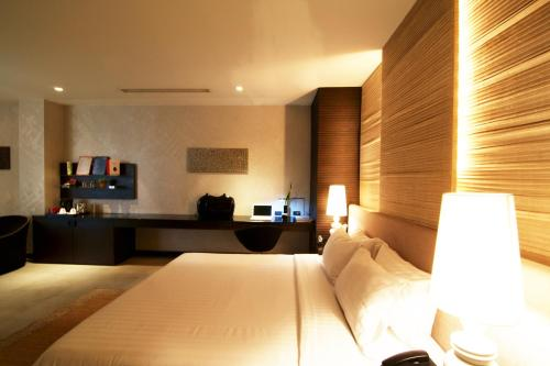 A bed or beds in a room at Dune Hua Hin Hotel