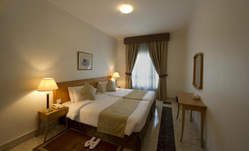A bed or beds in a room at Al Bustan Centre & Residence