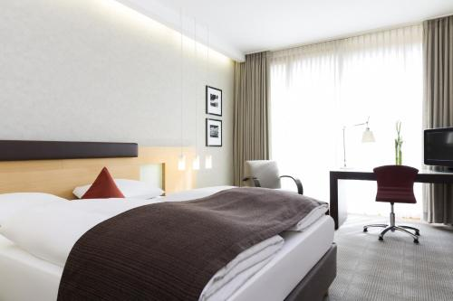 A bed or beds in a room at Novotel Karlsruhe City