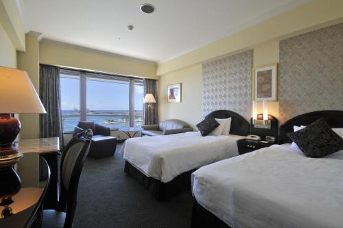 A bed or beds in a room at Okinawa Kariyushi Urban Resort Naha