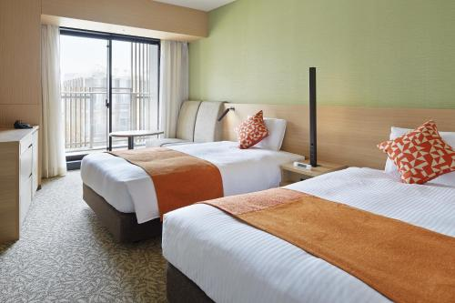 A bed or beds in a room at Mitsui Garden Hotel Kashiwa-No-Ha
