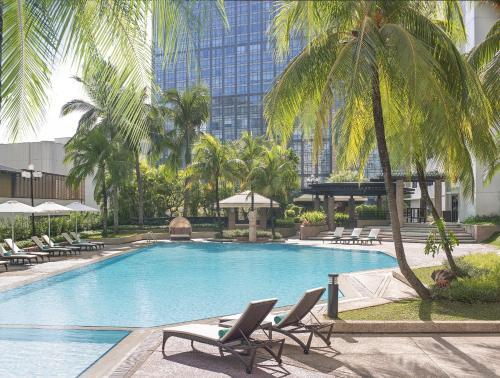 The swimming pool at or close to New World Makati Hotel, Manila