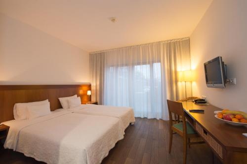 A bed or beds in a room at Tisza Balneum Hotel