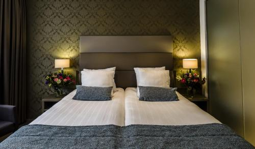 A bed or beds in a room at Ozo Hotel