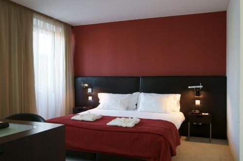 A bed or beds in a room at Hotel Jeronimos 8