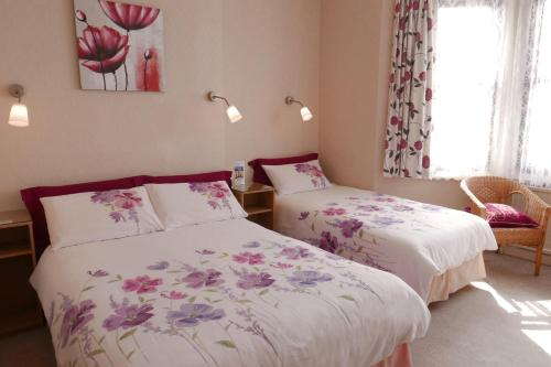 A bed or beds in a room at Abbey Guest House