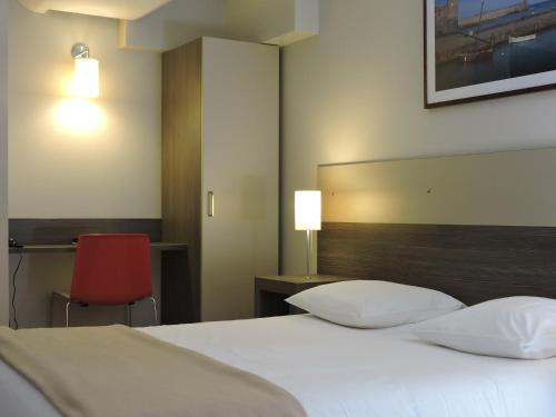 A bed or beds in a room at Logis Hotel Prime - A709