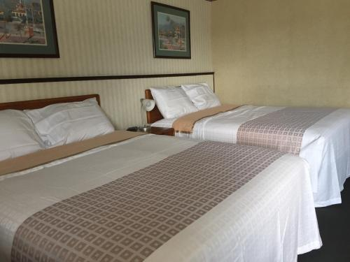 A bed or beds in a room at Stay Plus Inn