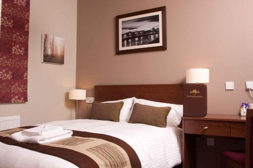 A bed or beds in a room at Wellington Hotel by Greene King Inns
