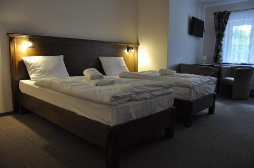 A bed or beds in a room at Pensjonat Leśniczówka