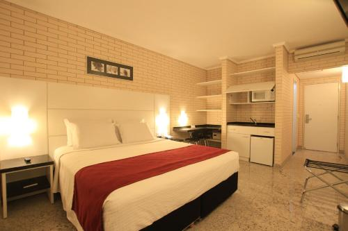 A bed or beds in a room at Hotel Confiance Prime Batel