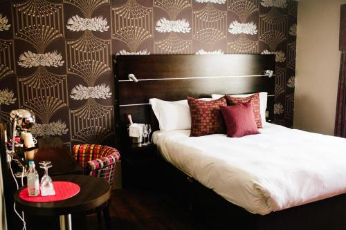 A bed or beds in a room at The Ashbourne Hotel