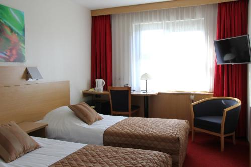 A bed or beds in a room at Bastion Hotel Leiden Voorschoten