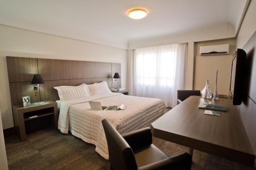 A bed or beds in a room at Slaviero Essential Curitiba Centro
