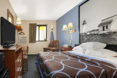 A bed or beds in a room at Super 8 by Wyndham Massena NY