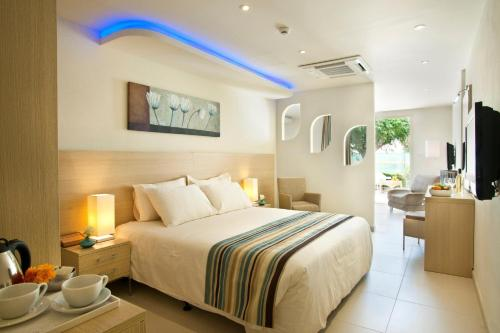 A bed or beds in a room at Pernera Beach Hotel