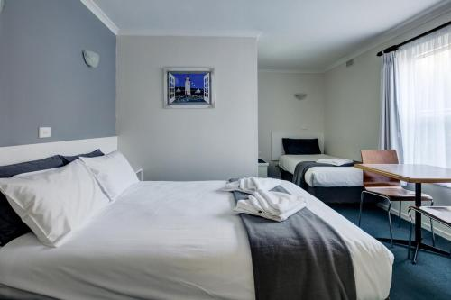 A bed or beds in a room at Central Motel Port Fairy