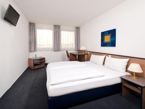 Кровать или кровати в номере ACHAT Hotel Monheim am Rhein