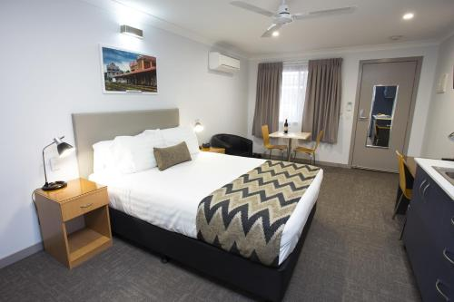 A bed or beds in a room at Altitude Motel Apartments