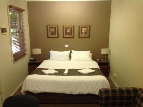 A bed or beds in a room at Coach House Inn