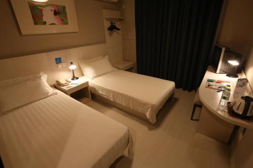 Кровать или кровати в номере Jinjiang Inn Jining Pipashan Road