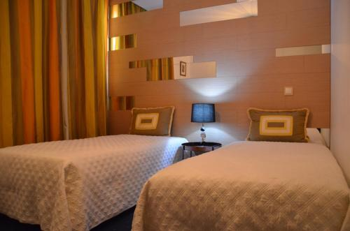 A bed or beds in a room at Hotel Abade João