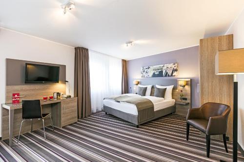 A bed or beds in a room at Leonardo Hotel Nürnberg