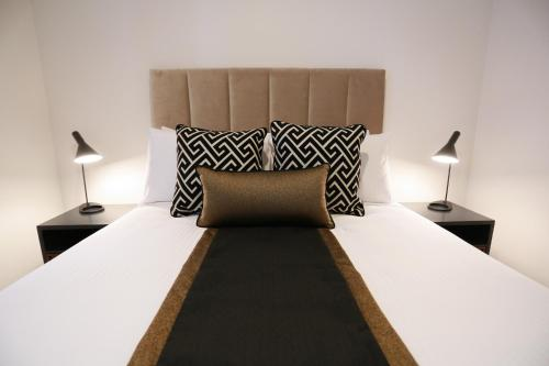 A bed or beds in a room at Alex Perry Hotel & Apartments