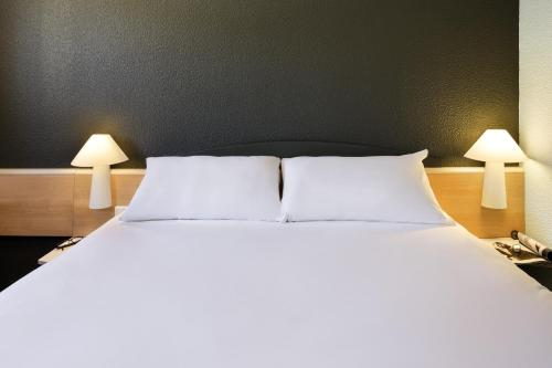 A bed or beds in a room at Fabrègues Hotel A9 Montpellier Sud