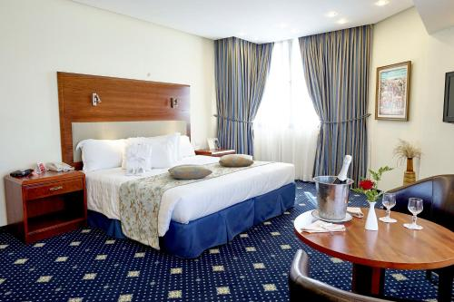 A bed or beds in a room at Ramada Jerusalem Hotel
