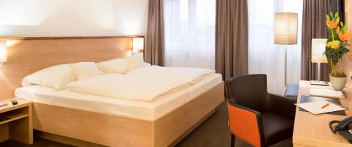 A bed or beds in a room at Stadthotel am Römerturm