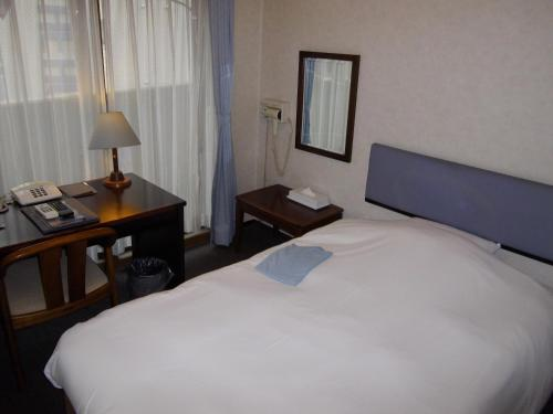 A bed or beds in a room at Hotel Business Villa Omori