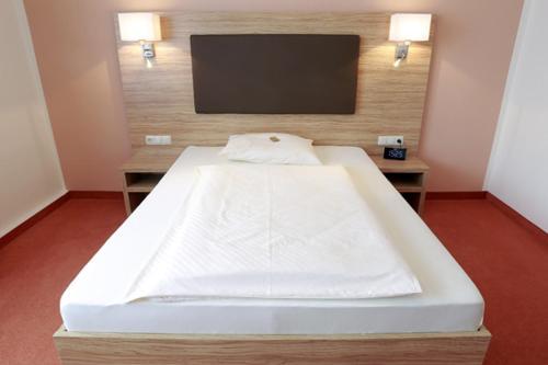 Ein Bett oder Betten in einem Zimmer der Unterkunft Hotel Falkenhagen