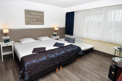 A bed or beds in a room at Hotel Herbergh Amsterdam Airport