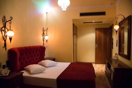 A bed or beds in a room at Alfa Hotel