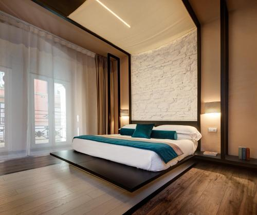 A bed or beds in a room at Dharma Luxury Hotel