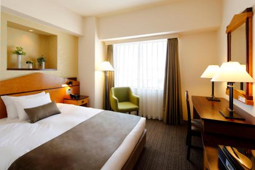 A bed or beds in a room at Hotel Resol Gifu