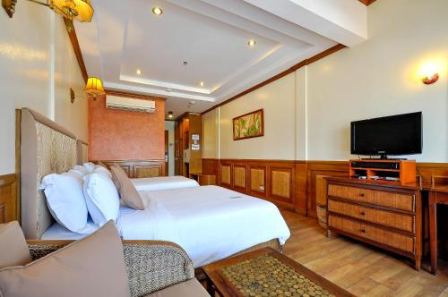 A bed or beds in a room at Red Coconut Beach Hotel Boracay
