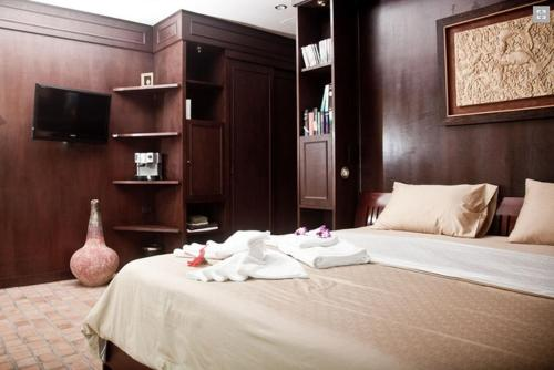 A bed or beds in a room at Noble Crown Resort & Spa
