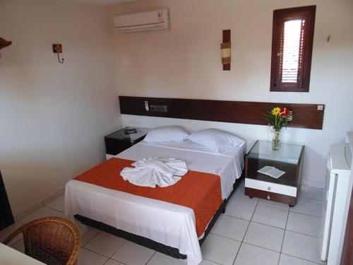 A bed or beds in a room at Pousada Solar Ponta Negra