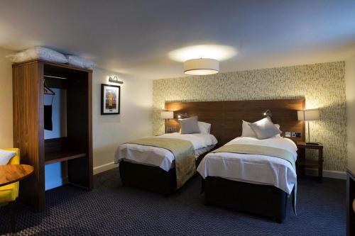 A bed or beds in a room at The Cross Keys Wetherspoon